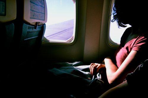 飛行機の窓側で座る女性のイメージ