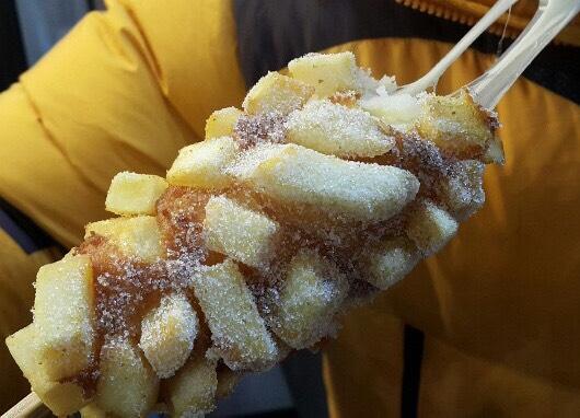 ジャガイモドッグからチーズが伸びている画像
