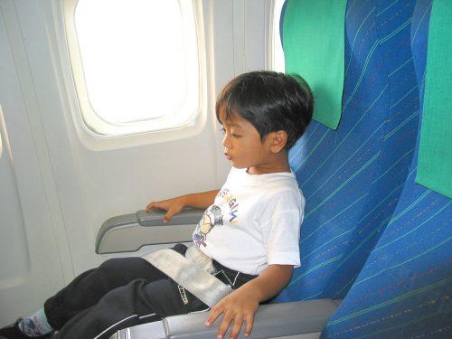 飛行機の窓側で座る子供のイメージ