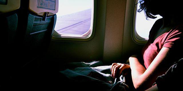 飛行機の窓から外を眺める